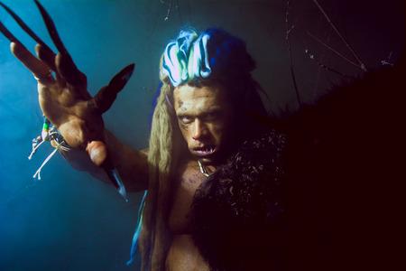 unas largas: Hombre lobo con las u�as largas y los dientes torcidos entre las ramas del �rbol y el humo azul. imagen g�tica de criaturas diab�licas de miedo para Halloween Foto de archivo