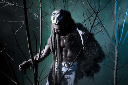 Muscular Werewolf Among The Branches Of The Tree. Gothic Image Of Scary  Diabolical Creatures For