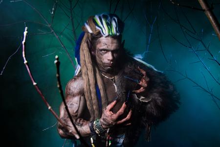 unas largas: hombre lobo muscular con los dreadlocks con los clavos largos entre las ramas del �rbol y el humo. imagen g�tica de criaturas diab�licas de miedo para Halloween Foto de archivo