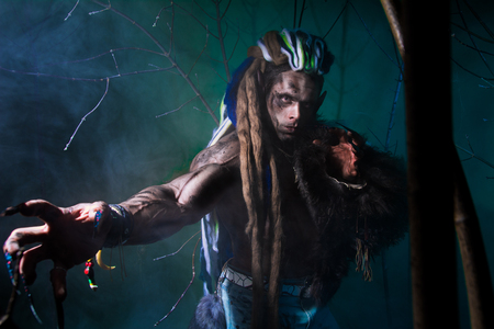 dark elf: Muscular werewolf with dreadlocks with long nails among the branches of the tree and smoke. Gothic image of scary diabolical creatures for Halloween