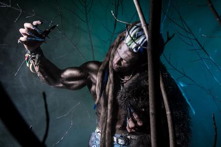 unas largas: Hombre lobo muscular con rastas con las u�as largas entre las ramas del �rbol. Imagen g�tica de criaturas diab�licas de miedo para Halloween