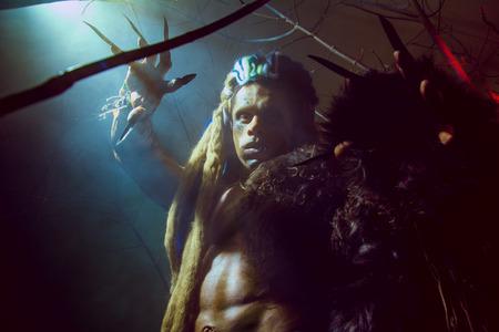 Weerwolf met lange nagels en scheve tanden tussen de takken van de boom en rook. Gotische beeld van enge duivelse wezens voor Halloween Stockfoto