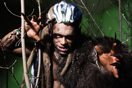 crooked teeth: Werewolf with long nails and crooked teeth among the branches of the tree. Gothic image of the diabolical creature for Halloween Stock Photo