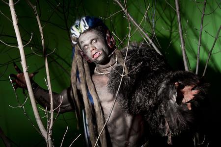 unas largas: Hombre lobo con las u�as largas y los dientes torcidos entre las ramas del �rbol. Imagen g�tica de criaturas diab�licas de miedo con los ojos cerrados para Halloween