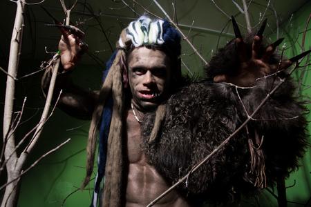 unas largas: Hombre lobo con las u�as largas y los dientes torcidos entre las ramas del �rbol. Imagen g�tica de criaturas diab�licas de miedo para Halloween Foto de archivo