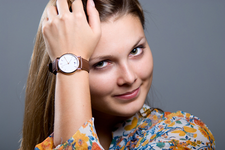 girl with a wristwatch: Close-up portrait of young beautiful girl in a bright colored blouse with a wristwatch on a gray background looking at the camera. Stock Photo