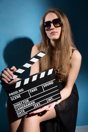 girl on a beautiful background: Beautiful woman holding a movie clapper. Cheerful girl helps in shooting a movie. Isolated on a white background