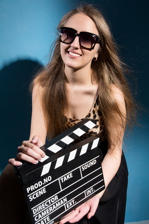 cute girl: Beautiful smiling woman holding a movie clapper. Cheerful girl helps in shooting a movie. Isolated on a blue background Stock Photo