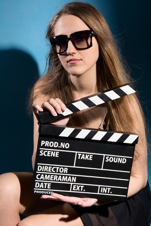 cute lady: Beautiful woman holding a movie clapper. Cheerful girl helps in shooting a movie. Isolated on a white background