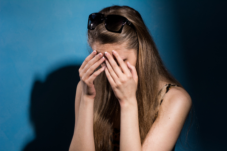 hands covering face: Sad woman covering her face with hands. On a blue background. Depression in young girls
