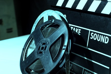 film shooting: Close-up reel of film against the backdrop of flappers for film shooting Stock Photo