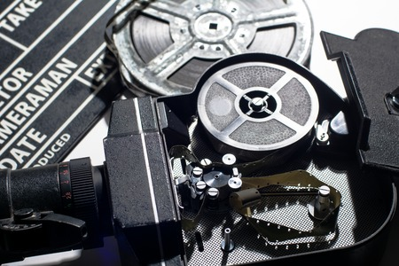 clap: Movie Camera with the lid open. Reel with film and cinema clap. Stock Photo