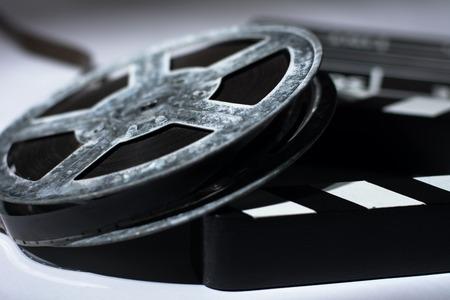 Old rusty metal reel of film and cinema clap.