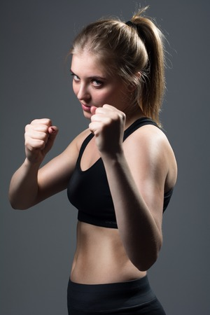 Girl with fists in rack. Young beautiful aggressive woman with fists in defense against dark background