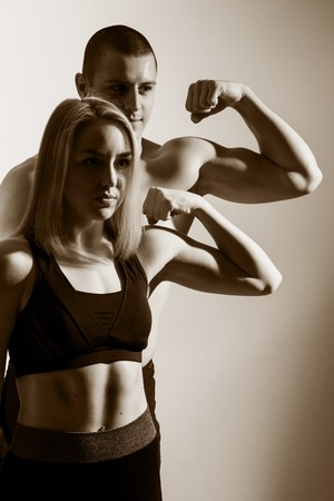 flex: Guy and girl flex biceps. Muscular couple flexing arms. Show me the bicep peak. How to build big arms.