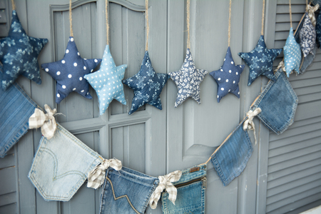 decorate: Decoration of fabric hanging stars on a background painted gray wooden trellis doors