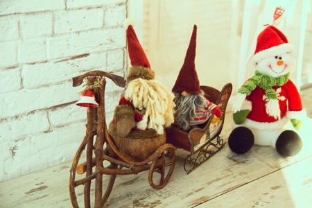 Gnomes biking and sledding and snowman standing on the wooden floor in the brick wall background Stock Photo