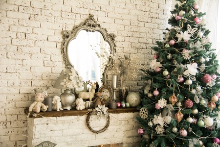 mantel: Background brick wall with a mirror Christmas spruce. Toys and figurines on mantel.