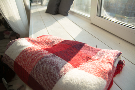 red plaid: Checkered red plaid on white wooden windowsill. Stock Photo