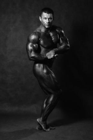 Muscular male Bodybuilder posing in studio over black. Monochrome image photo