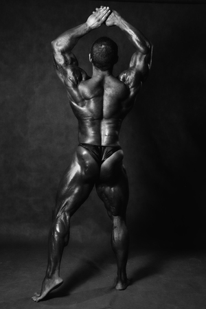 Muscular male Bodybuilder posing in studio back over black. Standard pose bodybuilder photo