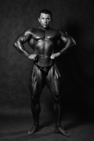 Muscular male Bodybuilder posing in studio over black. Standard pose bodybuilder. Monochrome image photo