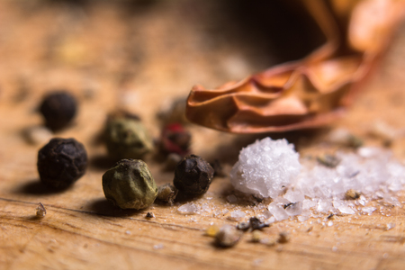 Close-up of pepper and salt. On a wooden board and ground peppers