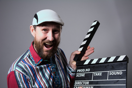 Close-up of a man smiling clapperboard cinema. Bearded man movie production of the comedy The assistant Stock Photo