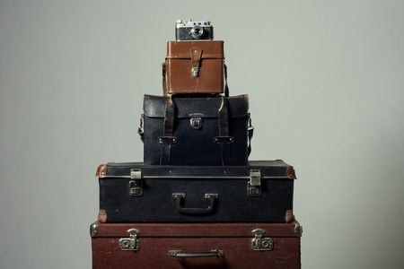 duffel: Stack of old shabby suitcases and camera. Concept traveler distant countries. Wardrobe trunk reportage photographer