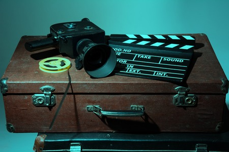 Old movie camera clapper and reel with film lie in two suitcases