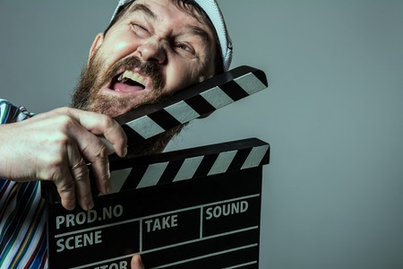 Smiling man with clapper movie. Bearded man movie production of the comedy The assistant