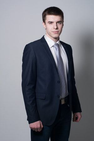 Portrait of confident business man on a gray background. Young man in a suit in the studio