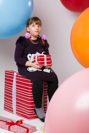 Thoughtful teenage girl with gifts on the background of large rubber balls. The girl with pigtails looks aside