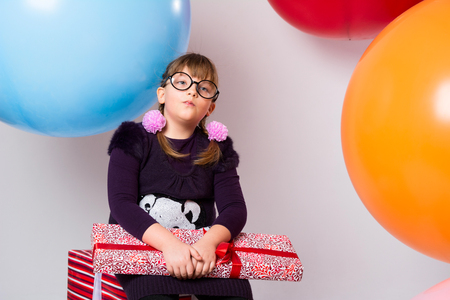 Thoughtful teenager with glasses and gifts on the background of large rubber balls. The girl with pigtails looks aside Фото со стока