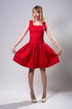 looking away from camera: Young smiling woman standing while showing red dress. Cheerful girl in full growth in the studio on a light background