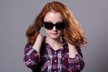 Close-up portrait of a red-haired beautiful woman wearing sunglasses. Young girl isolated on gray background