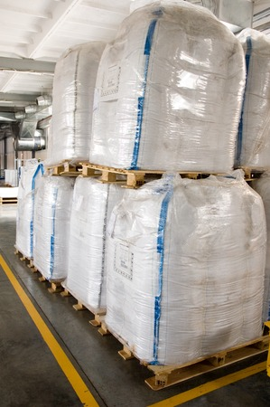 White large containers for bulk material on pallets. Bags for polycarbonate, chemicals and cereals in a dry warehouse