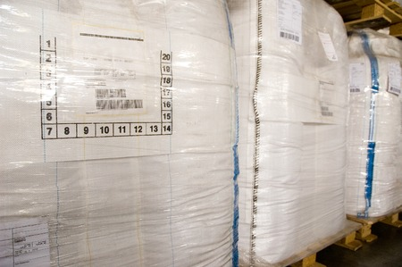 warehouse building: White large containers for bulk material on pallets. Bags for polycarbonate, chemicals and cereals in a dry warehouse
