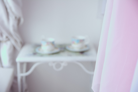 comfortable: Background tulle and in blur two cups and saucers on a metal table.