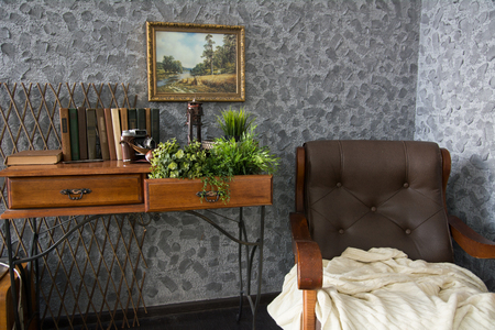antique vase: An old leather armchair with a rug and a chest of drawers with books. Interior of a room with a picture on the wall