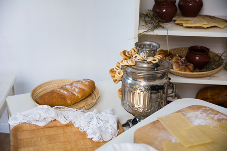 Samovar with the sheep on the table and the loaf in the wicker Stock Photo