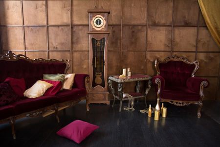 Interior Of A Beautiful Old Room With Red Armchairs Against A Wooden Wall  With A High