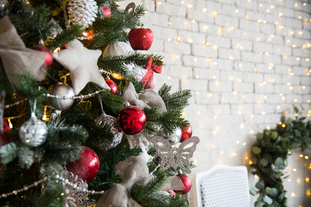 xmass: Christmas tree with red balls and self-made stars on the background of a brick wall with garlands and a Christmas wreath