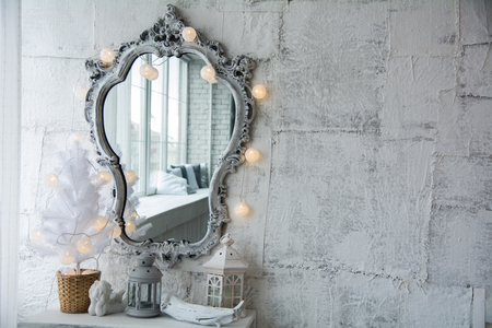 Mirror in an old frame and a white Christmas tree with a garland and white balls on the table. Mirror background of an old cloth wall