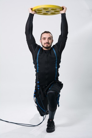 Fitness man in an electric stimulation suit on a white background in studio in full growth. A muscular sportsman with a kettlebell of yellow color Stock Photo