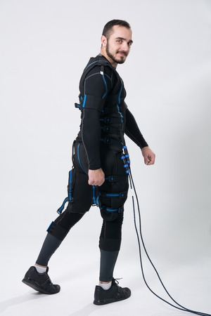 Young fitness man in an electric stimulation suit on a white background in studio in full growth Stock Photo