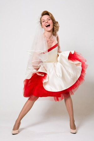 Emotional bride in a red white dress. Happy young woman in wedding dress in full length on a white background in studio