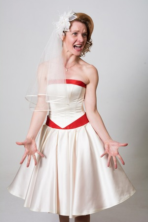 Brides portrait of the indignant screams to the side. Displeased woman in a wedding dress on a white background