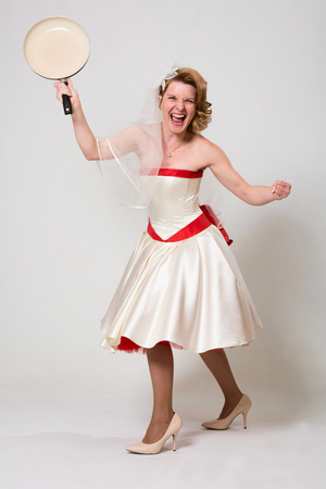 Beautiful angry bride waving a frying pan. Woman in wedding dress in full length on a white background in studio Banco de Imagens