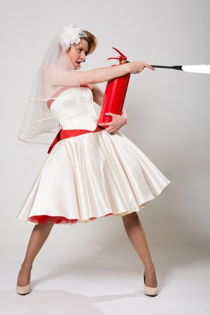 Bride with fire extinguisher on white background in studio in full length